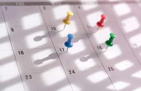 Thumbtacks pin on calendar. Concept for busy schedule.