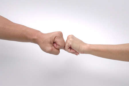 Close up of fist bump of a man and woman's hands against white background.