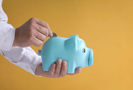 Man's hand putting coin to piggy bank. Yellow background, copy space.