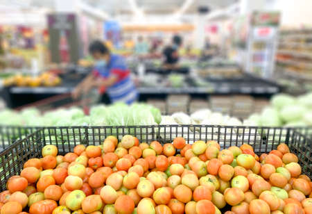 Shopping inside supermarket grocery section, defocused. Selective focus on tomatoes.