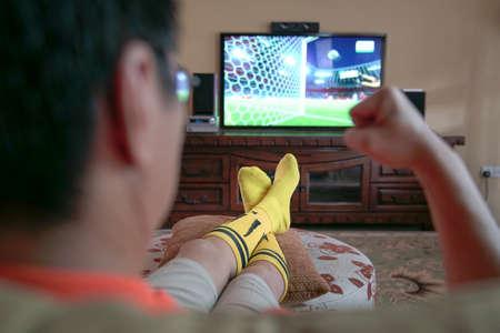 Man watching sport on tv. Fist in jubliation when football goal scored on screen.