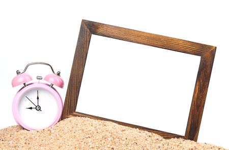 wooden picture frame and alarm clock on the beach