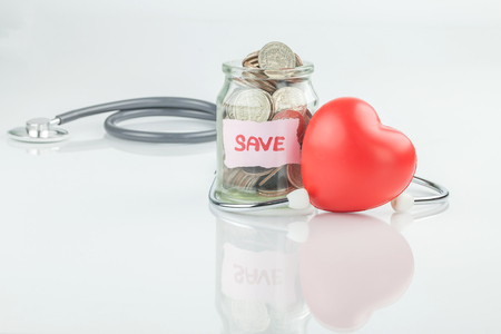 Jar of saving coin and stethoscope