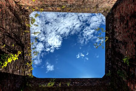 Blue sky in hole in old wall, brick frame.selective focus.
