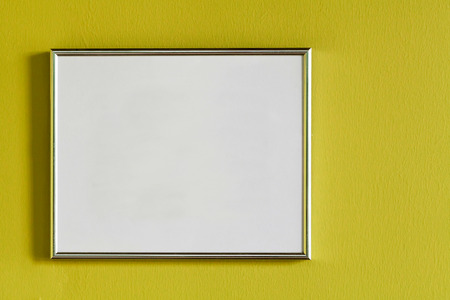 Blank photo frame on the yellow  wall