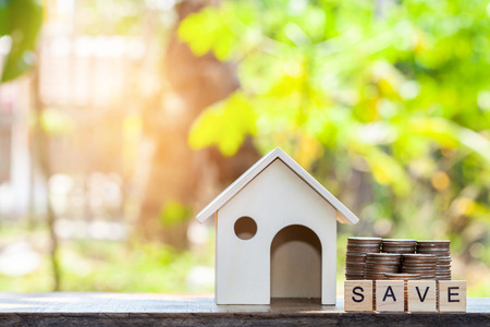 coin stack with house model, savings plans for housing ,blur background, financial concept Reklamní fotografie