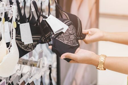 Women's hands are holding a Lingerie at shop woman underwear clothes in the shopping mall.