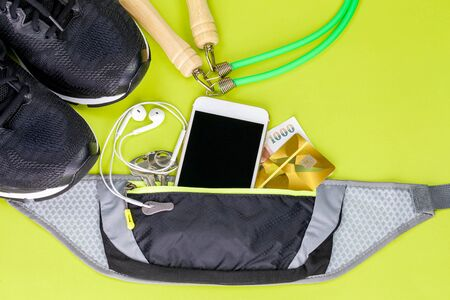 jumping rope, athletic shoes and sport equipment on green background