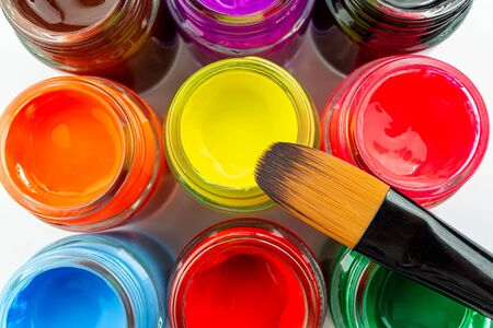 Multicolored bottles poster color and paintbrush on a white background Isolated Paints in containers Top view Copy space