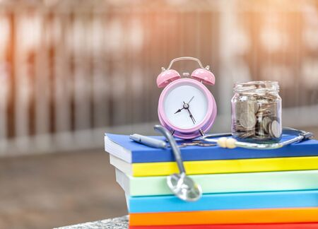 pink alarm clock closeup standing on pile of books. Business or education concept