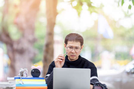 Portrait of male student sitting at the park and using laptop , writing thesis with serious face expression. Young asian man working on his home assignment Stock fotó