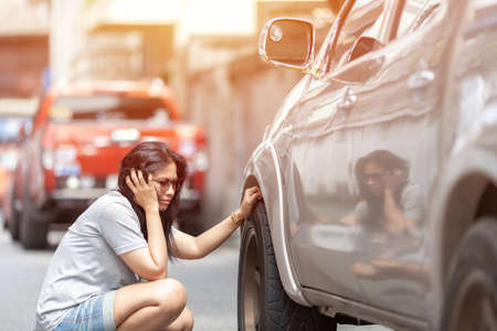 Sad asian young beautiful woman  with worried stressed face expression looking down in car wheels with copy space