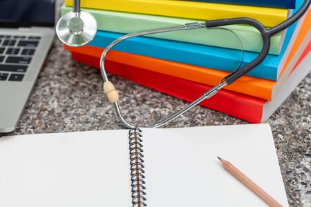 Medical stethoscope with notepad and books on desk, medical concept. Banco de Imagens