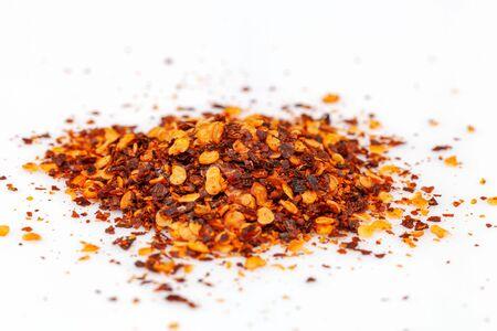 Haufen zerkleinerter roter Cayennepfeffer, getrocknete Chiliflocken und Samen isoliert auf weißem Hintergrund Standard-Bild
