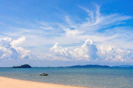 A boat in the sea of blue and crystalline waters of Paraty. The sea advancing in the sand. Mountains and blue sky with clouds in background.