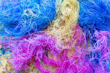 Multi-colored tangled threads abstract texture pattern background. Macro shot of colorful needlecraft silk thread ropes.