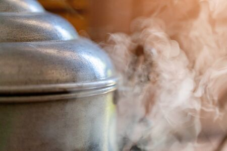 Closeup of vintage stainless steel pot and steam cooking in  kitchen Banco de Imagens
