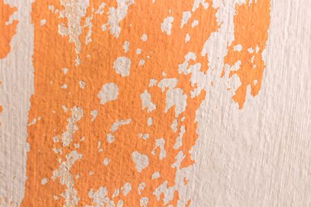 Old weathered painted wall background texture. orange dirty peeled plaster wall with falling off flakes of paint