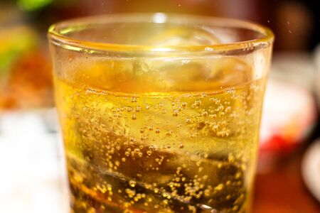 Glass of Whisky (whiskey), bourbon, ice tea or coke (cola) soda with ice and water drops on wood table at blur background