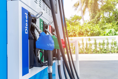 A petrol pump gun in a petrol station. Close up on fuel nozzle in oil dispenser with gasoline and diesel in service