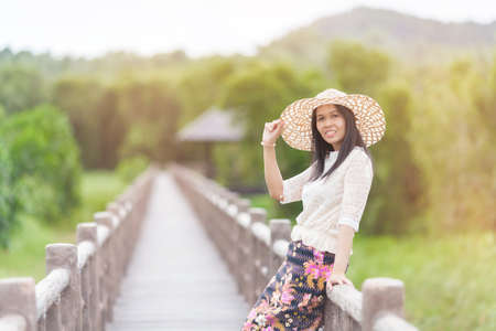 wooden rustic bridge, spring scene,  with  hat enjoying the day in a park