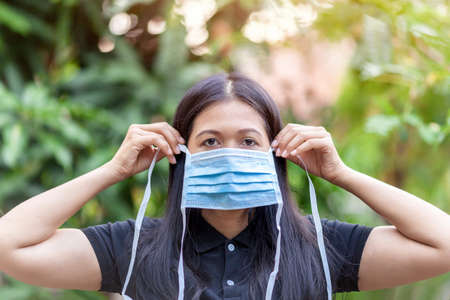 Portrait of Asian Young woman wearing Medical Health Mask, Promoting people use face mask to protect themselves from virus infection in Corona virus crisis 2019