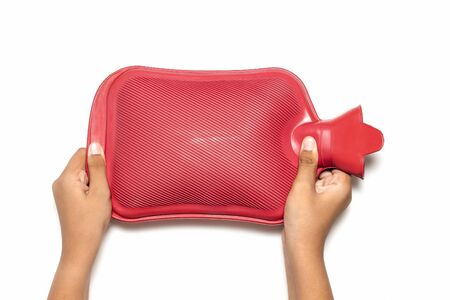 man holding in hand red hot water bottle  on white background. Health care, pain relievers, treatment objects concept