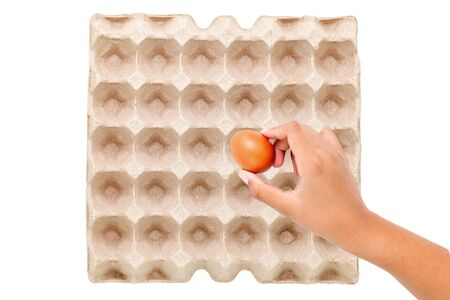 Chicken brown eggs in egg carton box with hand holding an egg on white background Stock fotó