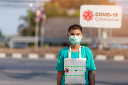 COVID-19 Pandemic Coronavirus Child in city street wearing face mask protective for spreading of Coronavirus Disease 2019. Portrait of child with face mask against SARS-CoV-2.