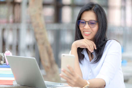 business woman in glasses works with a smartphone in a cozy park