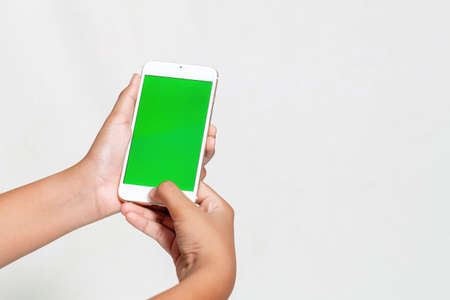 Woman hand holding the white smartphone with green blank screen isolated on white background
