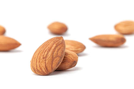 nutritious  almonds scattered on white background with blurry