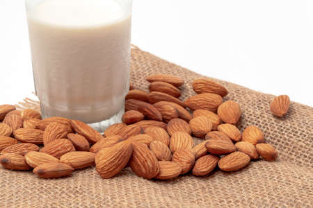 Organic white almond milk in a glass  with whole almonds spilled over a white table. Focus on nutmilk with blurred background.
