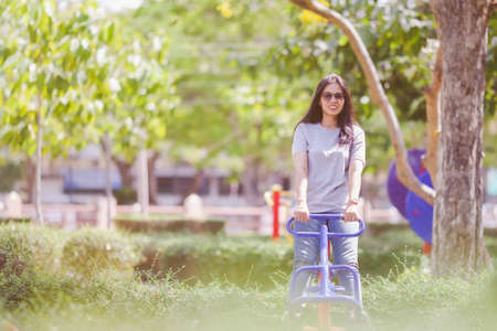 Portrait of beautiful young woman exercising in the park. Asain female fitness model working out in the morning. Confident fitness model in park. Active sporty woman enjoying outdoors in autumn.