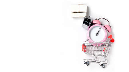 alarm clock in a pink plastic case and black hands in a metal shopping cart with tally click counter on a white background selective focus isolated 版權商用圖片