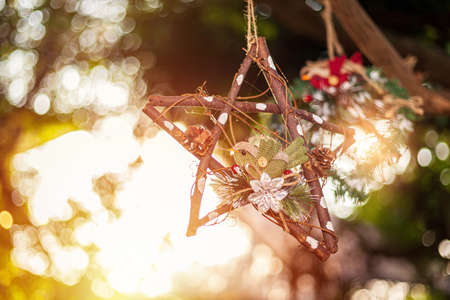 New Year and Christmas toy in a shape of brown star hanging on a Christmas tree surrounded by other toys and lights.