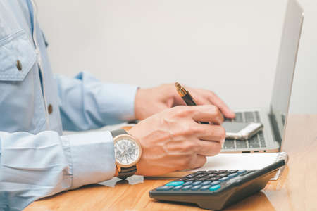 male accountant making calculations,reviewing data in financial charts and graphs  at work place. Business financial  concept.