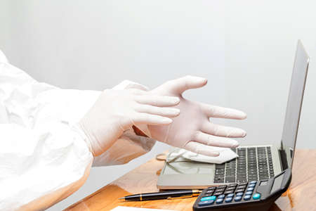 business men wear rubber gloves to working  with laptop at wooden table
