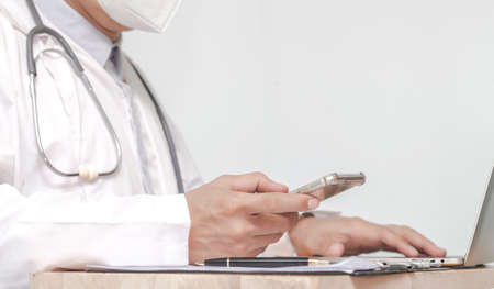 male doctor texting on smartphone in medical office