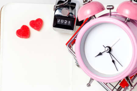 Alarm clock, red jelly heart on a white background. Good morning or working space. Flat-lay, top view. 版權商用圖片