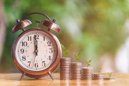 Money coin stack growing graph with alarm clock to profit concept investment business and finance