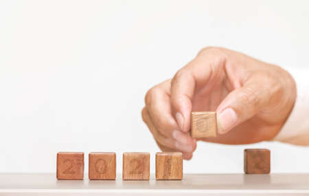 Hand is changing a wooden cube symbolically changes from 2020 to 2021