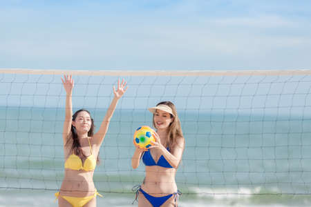 Two happy young girlfriends playing volleyball at the tropical beach, unfocused