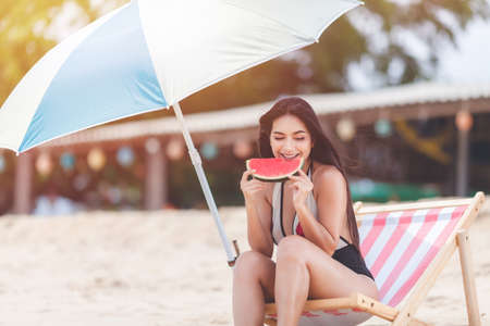 Happy summer and vacation , holiday , long weekend on the beach. sexy woman relaxing wearing  bikini sitting on beach chair , and watermelon tropical fruit ,smile and relax