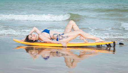 attractive sexy young asian woman surfer girl in bikini   poses on sandy beach with surfboard , water sports, healthy active lifestyle, summer vacation, extreme sport.