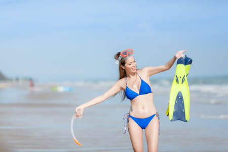 Beach woman walking by ocean. Girl in bikini with snorkel coming out of water after swimming and snorkeling in beautiful blue ocean .
