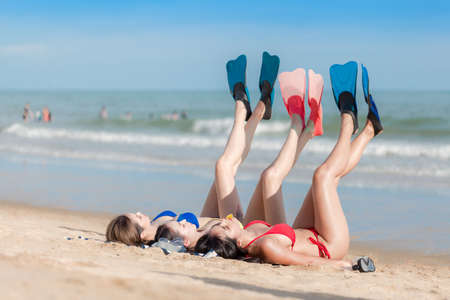 Three beautiful girls on the beach lying on the sand Stock fotó