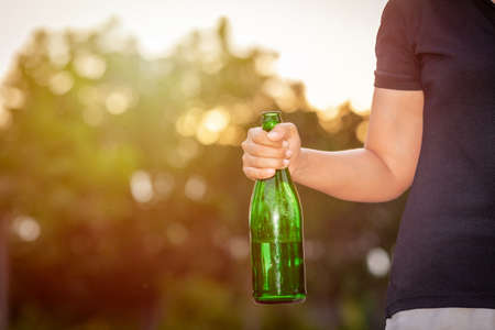 close up young woman holding a green bottled beer  with his hand Stock fotó