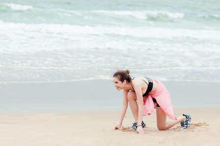 Sports and Jogging along the sea. A young brunette woman stands ready to run. In the background Stock fotó