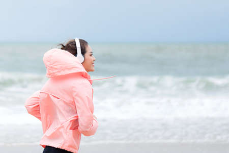 Young fitness running woman jogging  on beach near ocean or sea on a foggy misty morning. Fitness and healthy lifestyle concept